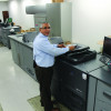 Oscar Rivera stands with one of the in-plant's two Konica Minolta bizhub PRO 1200s.