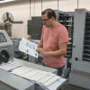 Carlos Padilla, main operator at UniPrint, reviews a proof coming off of the Standard Horizon StitchLiner 5500 saddlestitcher.