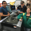 Staff at the University of Oregon's Print & Mail at the University of Oregon. The 21-employee shop operation gather around their brand new Duplo DC-646 slitter/cutter/creaser. From left: Alonzo Costilla, Dave Juvenal and Beth Talbot.