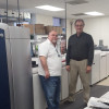 Standing with the new Xerox Color 1000i installed in January at Concordia University Wisconsin Auxiliary Services are Les Smith (left), print operator, and Mark Pfenning, manager.