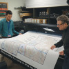 Michal Wyka and Antonio Buccini check the quality of a backlit print of a CTA system map produced on a 60˝ HP Designjet Z6100ps.