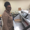 Print Production Specialist Deirdre Marsh operates the MBM Triumph 5560 cutter at Marist College's Digital Publications Center.