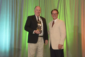 Doug Larson accepts the In-House Promotional Excellence award on behalf of his in-plant from IPMA awards chair Christopher Donlon.