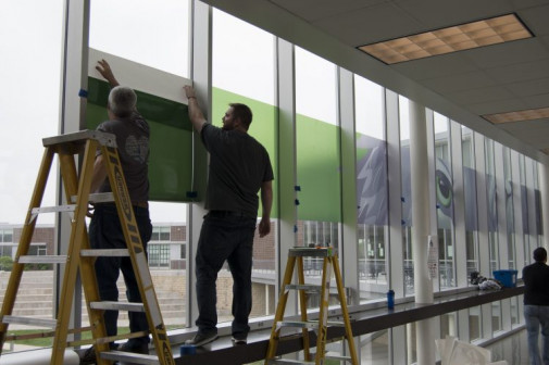 Rich Hayes (left), warehouse delivery driver, and Clay Herbison, production & logistics specialist, install a 75-foot long window cling graphic on the skywalk of a Blue Valley high school.