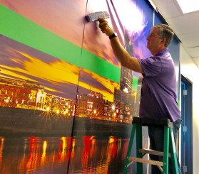 "Schneider ­Electric's Kris Tanner puts the finishing touches on a wall graphic installation. Whenever wide-format graphics need to go up at the company's field locations, he says, ""the installer is me."""