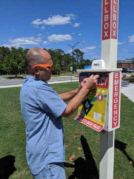 Steven M. Barrett, manager of SeaPrint Graphic Solutions at the University of North Carolina Wilmington, installs signage on a police call box on campus.