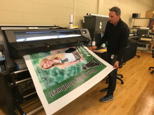 Paul Ackerman guides a poster out of the in-plant's HP Latex 310. Already in the 2018-2019 school year, the shop's wide-format work is up 141% over what it produced in the entire 2016-2017 school year.