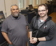 Carlos Trujillio (left) and Evan Harper stand with some of the in-plant's Konica Minolta equipment.