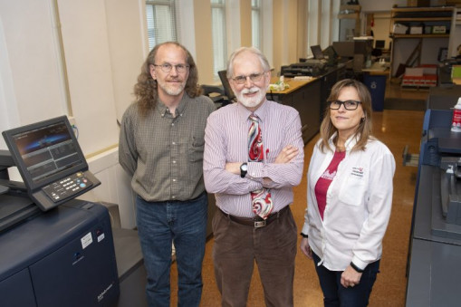 John Wesseling (center), director of Printing and Duplicating Services at the University of Cincinnati, stands with Bill Nienaber (left) and Karen Kappen inside one of his in-plant's facilities.