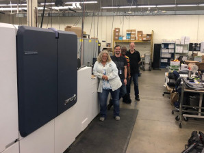 Print and Mail Management staff stand with the new cut-sheet Xerox Brenva HD inkjet press. From left: Shay Cooper, Brian Paquin, William Banks, and Steve Hodgman.