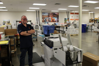 Greg Misoni stands next to the in-plant's Intoprint MP200 digital envelope printer.