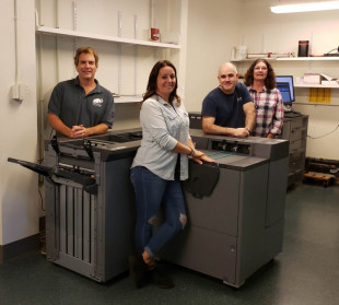 With the new Konica Minolta AccurioPress C3080 at the Amherst College Campus Print and Mail Center are (from left) Rod Squier, manager; Jennifer Kendall, print, bindery & mail technician; Robert Kleindienst, duplication & digital specialist; and Trish Connelly, mailing services specialist.