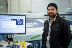 Operator Juan Martinez stands with the Océ Arizona 1260 GT flatbed printer.