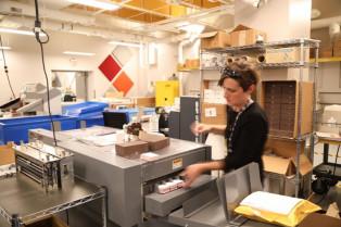 Misti Muller slits business cards on the in-plant's Duplo 645 slitter/cutter/creaser.