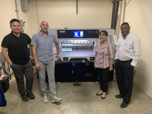 Multimedia Services Manager Dagnu Bezu (far right) and team members at the Alameda County Sheriff's Office stand with the new SABER X-15 paper cutter.