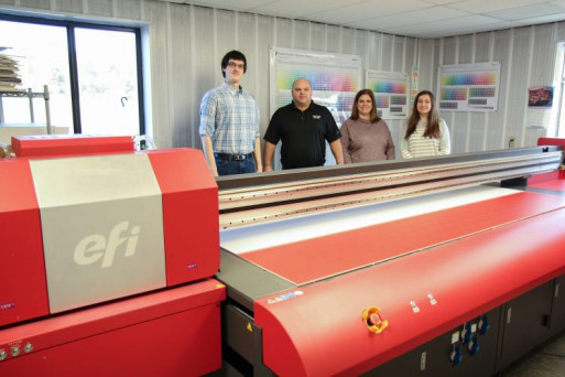 Print and Mail Services staff stand behind the EFI Pro 24f LED flatbed printer. From left: William Lenz, Dave Earp, Amanda Latch, and Emily Bowling.