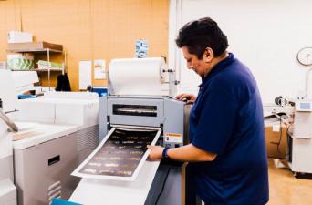 Sam Echevarria runs a piece through the new Duplo DFL-500 coat/foil/laminator.