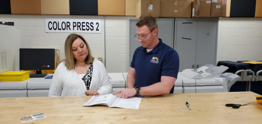Sherri Broderick (left) and Jason Almand inspect curriculum materials produced by the in-plant.
