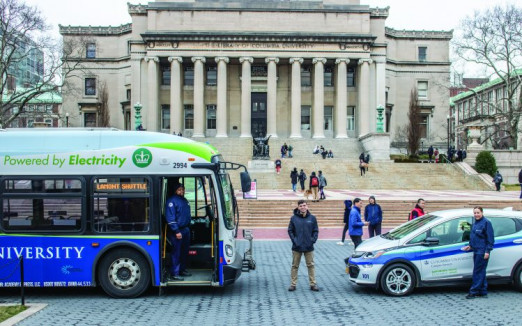 To reduce CO2 emissions, the in-plant uses a clean energy fleet of vehicles to pick up and deliver campus mail, including this electric Chevy Bolt (right). The university has also added six electric buses to its shuttle fleet. Showing them off are (from left) Jameel Henry, Neftali Rivera, and Jeannette Tapia.