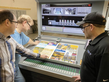 Director Jeff McNeeley (left) inspects a printed sheet at the press console with operators Alan Dickinson and Todd Dolan.