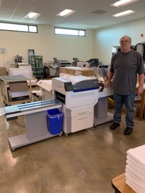 lDennis Winters stands with Printing and Graphics Services' new OKI C931E digital envelope press, which has improved the quality of the in-plant's envelope printing.