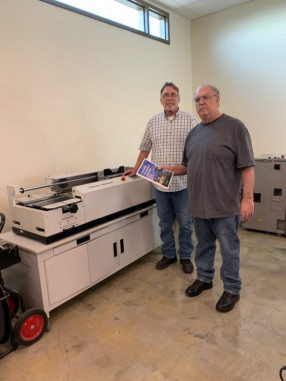 Installing a Sterling Digibinder has allowed the in-plant to keep perfect binding jobs in-house, reducing outsourcing. With it here are Kevin Sutton (left) and Dennis Winters.
