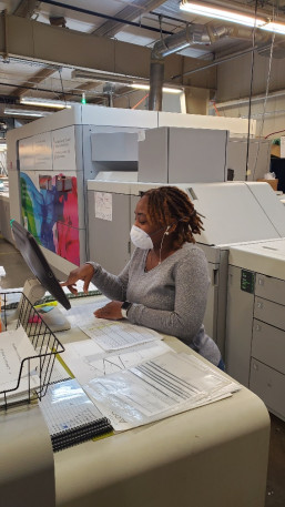 At Houston Independent School District Printing Services, Darian Craver runs the Canon VarioPrint i300 inkjet press, wearing typical in-plant facial attire in the age of COVID-19.