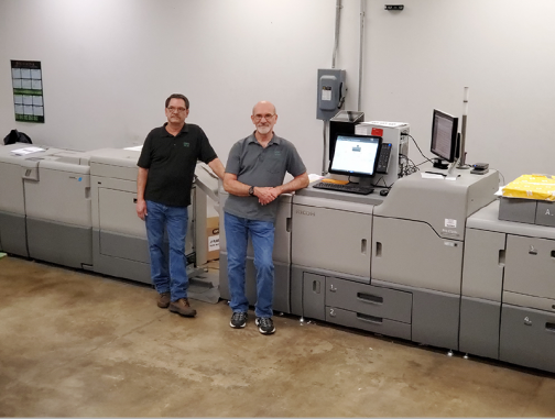 Earl Callahan and Grady Miles stand with the new Ricoh Pro 7210X.