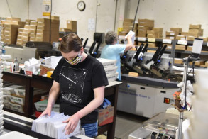 Face mask in place, Publishing & Distribution staff member Amanda Brown processes mail in the in-plant's production mail unit.