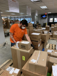 Wearing a mask and gloves, Jake Navarro moves packages at The University of Texas at Austin.