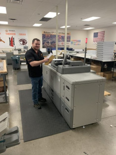 Printing K-12 curriculum materials has kept Deer Valley Unified School District Graphic Communications busy all spring. Here, Kevin Ahern holds up homework packets printed on the in-plant's Ricoh Pro 8210.