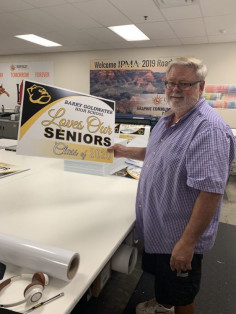 Yard signs congratulating seniors have kept many educational in-plants busy during the pandemic. At Deer Valley Unified School District Graphic Communications, Gene Faken shows off a sign printed by the in-plant.