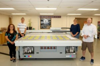 Showing off the new Canon Arizona 2280 XT flatbed printer at the Commonwealth of Pennsylvania's Bureau of Publications are (from left) Maria Martinez, sign technician; Benjamin McAfee, sign shop manager; Marcie Carr, bureau director; and Craig Andrews, graphics division chief.
