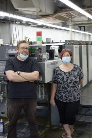 Manager Michael Czerepak and Assistant Manager Jo Ellen Rathbun stand with the University of Delaware's five-color Komori Lithrone press.