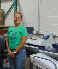 Lisa Jackson stands with the Pitney Bowes DI950 four-station inserter.