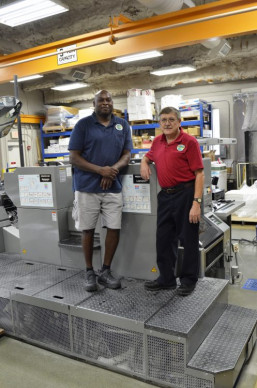 Standing with the four-color, 14x20˝ Presstek 52DI digital offset press he runs at the Palm Beach County Graphics Division, Talmedge Hayes (left) poses with Manager John D.L. Johnson.