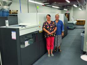 Pam Dye (left) and Kelli Embry stand with Shelter Insurance Document Services' Kodak NexPress SX3300.