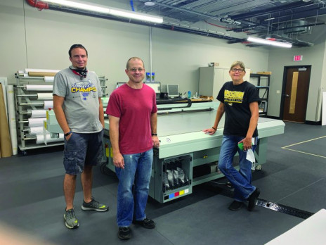 Standing with the Canon Arizona 365 GT UV flatbed printer at Shelter Insurance Document Services are (from left) Adam Schaefer, Tim Kreitner, and Susan Heath.