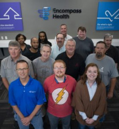Encompass Health Print Services employees. Front row, from left: Jeffrey Robinson, Adam McDowell, and Nicholle Smith. Second row, from left: Scott McCrary, Wendell Rotenberry, Mike Cochran, and Glenn Conway. Third row, from left: Teresa Harris, Derek Shackelford, Antonio White, Mark Tucker, Paul Deason, and Mike Mayfield. Far back: Director Danny Kirkland.