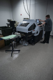 In the bindery, Paul Deason runs the in-plant's Horizon Cross Folder AFC-566F.