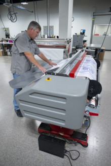 Scott McCrary cuts a job on the Fotoba XLD-170 digital cutter with X/Y trimming. Print Services was able to centralize all of its wide-format equipment in the new facility.