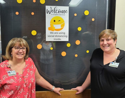 Lisa Pitts (left), division manager of Graphic Services for the City of Greensboro, and Mary Brookshire, assistant manager/graphic designer, stand in front of their in-plant's decorated office window.