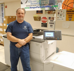 Walter Ryan, Print Shop foreman for the City of Bangor, poses next to his in-plant's Ricoh Pro C5100s.