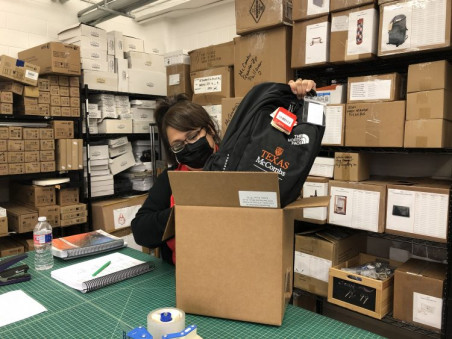 Missy Lopez boxes a backpack, one of the UT-branded items ordered along with course packs via the in-plant's e-commerce site.