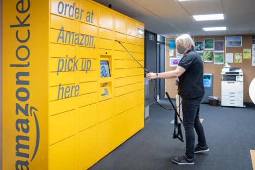 Nicky Doherty, customer services assistant, sanitizes the Amazon lockers.