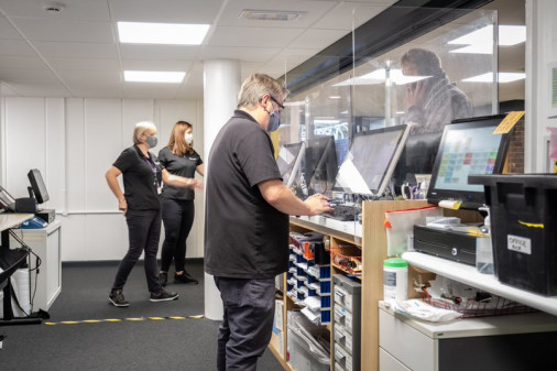 Richard Jackson (front) serves a customer, while Nicky Doherty and Ewelina Kalisz use the KxParcels system to identify and find parcels for customers.