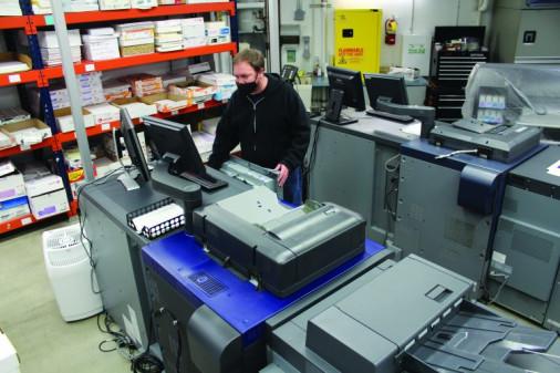 Lonnie Burgener runs a job on the in-plant's Konica Minolta AccurioPress C3070 digital color press.