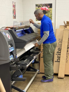 Print Production Specialist Chris Hicks prints a wide-format job on the in-plant's HP Latex 310.