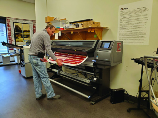 Troy Oakley prints a job with Elon University Print Services' new HP 365 wide-format latex printer and cutter.