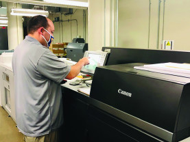 David Doerfler operates the Canon imagePRESS C10000VP digital color press.